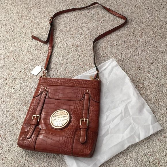 ❤️REDUCED❤️NEVER USED Cross body purse NEVER USED!  Brown cross body purse with gold color buckle and emblem.  Comes with dust bag for clean storage.  Impulse purchase from a boutique December 2015, but I changed my mind and couldn't return it.  😕 It's a really nice purse, just not my style. Bags Crossbody Bags