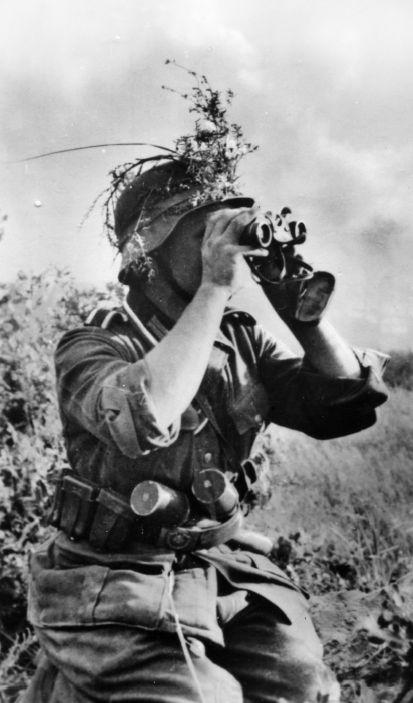 """""""Opération Barbarossa"""" de Hans Seidler Soldat observant le champ de bataille à l'aide d'une paire de jumelles 6x30 à prismes. Il porte au ceinturon deux grenades à manche modèle 1924, et a disposé sur son casque, à des fins de camouflage, des éléments de feuillage fixés au moyen d'un morceau de chambre à air."""