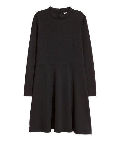 Schwarz. Kurzes Kleid aus festem Jersey mit kleinem Stehkragen und verdecktem Rückenreißverschluss. Lange Ärmel, Taillennaht und ein ausgestellter Rock.