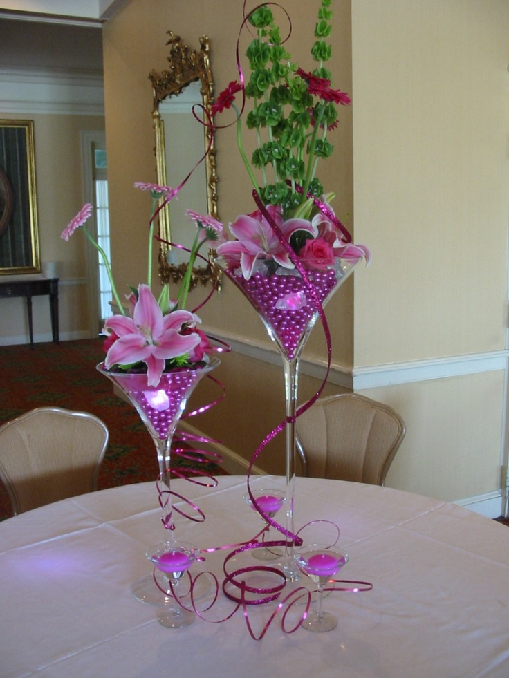 Centerpiece using Martini Glasses filled with hot pink pearls, small lights and flowers accented with coiled wire.