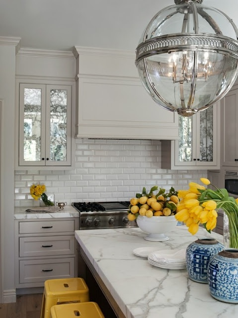 Love the subway tile splashback with the pop of colour in the tulips and yellow stools!