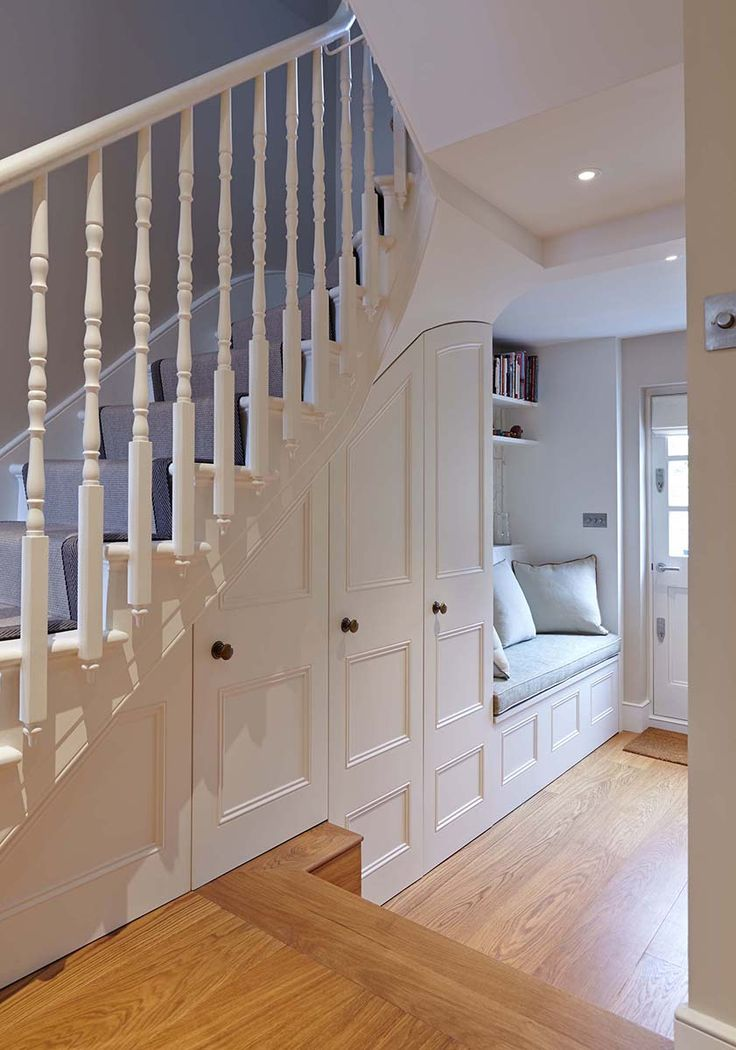 Garden room seating with custom fitted storage and cloak cupboard under the staircase