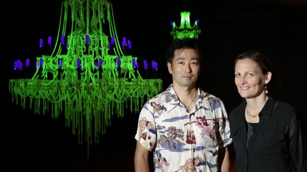Artists Ken and Julia Yonetani stand in front of their work USA 2013 a chandelier made from uranium glass.