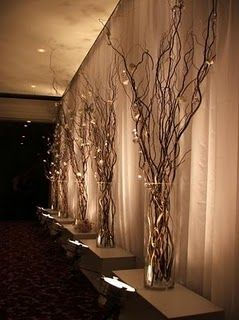 this could be a cheap option for creating warmth. uplights cost like 5 bucks each. i have some willow branches in a modern white vase at my house...i love it.