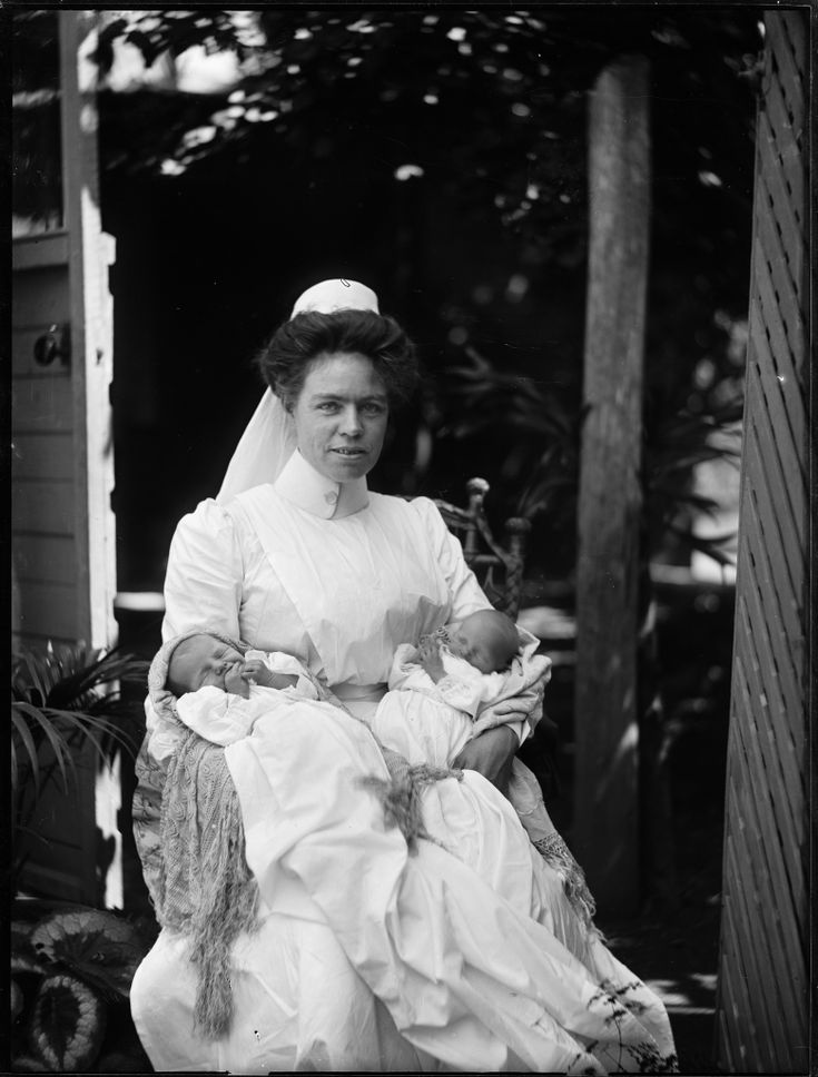 Portrait of a nurse in white, holding twin babies this photo was taken circa 1900.