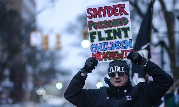 A protester poses for photo with his sign about Flint's water crisis. Michigan governor Rick Snyder has been accused of ignoring concerns over quality of the city's water supply.