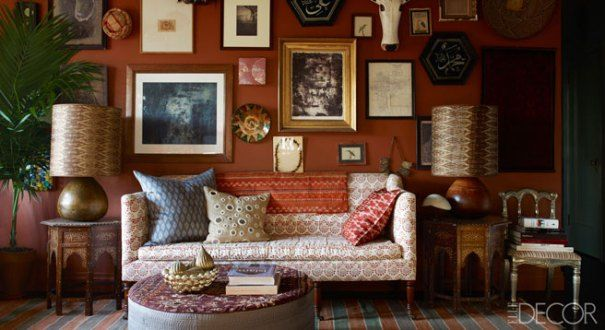 """John Derian sofa upholstered in linen by Robshaw and topped with his pillows. Bone-inlay side tables hold mango-wood lamps fitted with shades by Robshaw; a mask from an Indian market, Turkish calligraphy mirrors, and a wood cow sculpture adorn the wall, which is painted in Farrow and Ball's Red Earth."" Design: Sara Bengur and John Robshaw. Photo: William Waldron. Text: Ingrid Abramovitch. ""Home and Abroad: John Robshaw's New York City Home"" produced by Anita Sarsidi. Elle Decor."