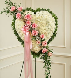 "This beautiful floral tribute shows your undying love during this difficult time. This standing spray arrangement in the shape of a heart is created from fresh white carnations, pink roses, Baby's Breath and more. Traditionally sent directly to the funeral home by family members or friends and displayed on a stand. Our florists use only the freshest flowers available so varieties and colors may vary. Measures approximately 24""H x 24""L without easel."