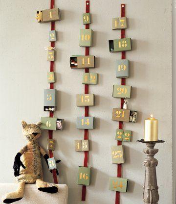 Calendrier de l'avent avec cases en forme de boîtes d'allumettes peintes et collées sur des rubans de velours