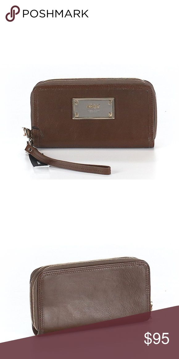 """NWT DKNY zip-around wallet NWT DKNY zip-around wallet/clutch in dark brown leather with metal logo plate on one side. Gold zippers and gold and silver faceplate. Like-new condition. 10"""" x 3"""" x 1"""". Smoke- and pet-free home. Make an offer! Dkny Bags Wallets"""
