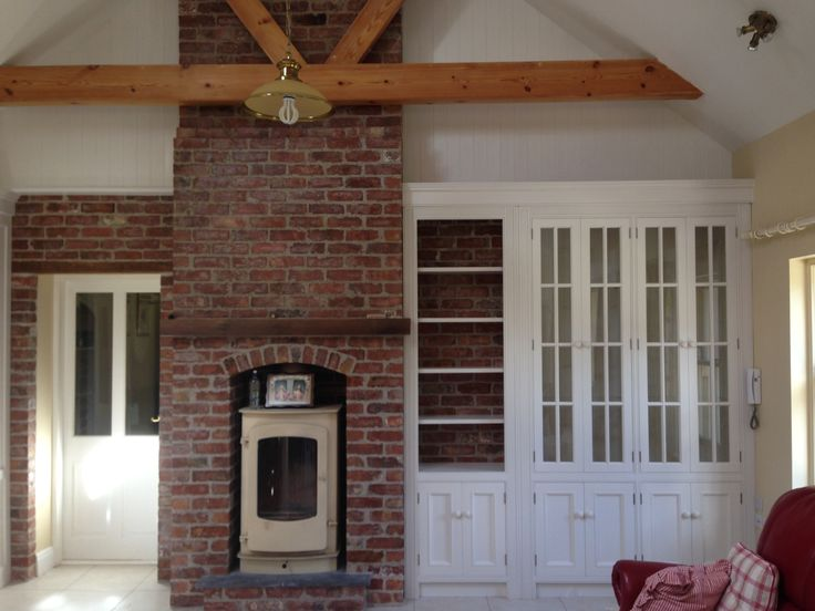 White painted book shelves in alcove next to red brick for Tiled chimney breast images