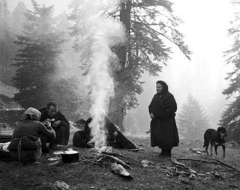 """ΤΑΚΗΣ ΤΛΟΥΠΑΣ-Γύρω από τη φωτιά Νέγρι 1975-Η αγάπη του για τη φύση και ιδιαίτερα για  βουνά τον οδηγούσε συχνά στον Όλυμπο και σαν δεινός ορειβάτης,έφτανε και στις πιο δύσβατες περιοχές.Έχοντας το χάρισμα να """"βλέπει"""" με ματιά που την χαρακτήριζε η ευαισθησία και ξέροντας να διαχειρίζεται με μαεστρία τα παιχνίδια του φωτός και της σκιάς,έχει αποτυπώσει τον Όλυμπο στις πιο όμορφες στιγμές του."""