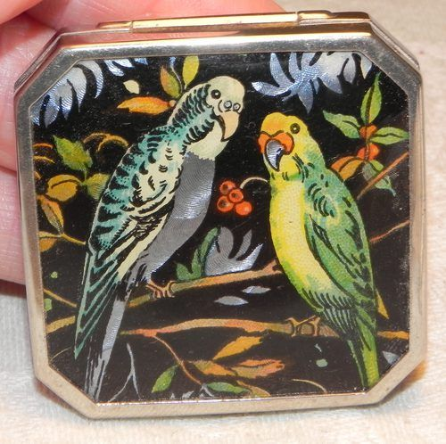 """Gwenda powder compact - dating c. 1930, it is in amazing vintage condition. Measuring c. 1.3/4"""" inch square with shaped corners, the gorgeous, vibrant colours of the foil picture depicting two budgerigar birds is set beneath a clear celluloid cover."""