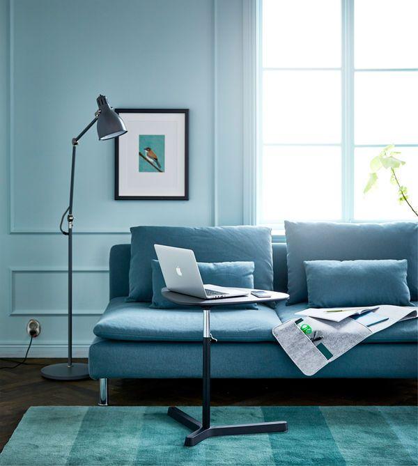 Stue med sofa, gulvlampe, hengende veggoppbevaring og et regulerbart laptopbord som fungerer som skrivebord ved sofaen