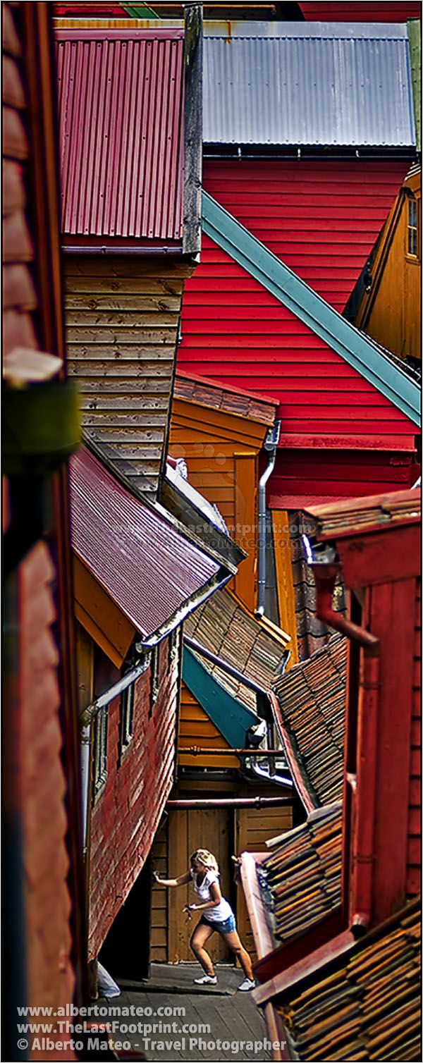 Woman closing the backyard of her shop,  Traditional Nordic houses, City of Bergen, Norway. Citiyscape Photography by Alberto Mateo, Travel Photographer.