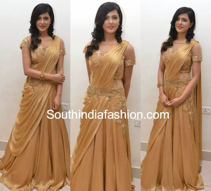 gold pre-stitched readymade satin lehenga gown featuring gold embroidered blouse with sheer neckline and sleeves and embroidered waist. A broad gold toned bracelet and curly hair finished off her look.