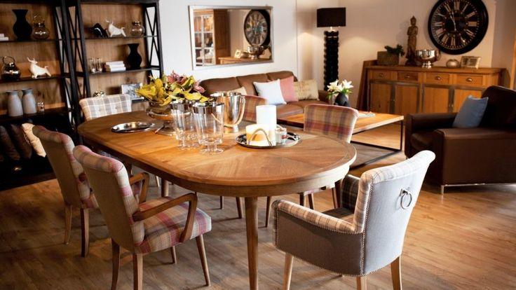 Owalny drewniany stół z kompletem krzeseł. Krzesła tapicerowane z podłokietnikami w różnych odsłonach: z ozdobnymi pinami, uchwytami bądź drewnianymi podłokietnikami. Stół i krzesła w klasycznym stylu przywołującym na myśl rodzinną atmosferę.