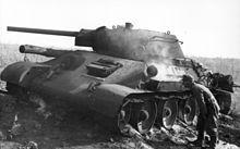Т-34 — Немецкий военнослужащий осматривает подбитый под Покровкой T-34 обр. 1941 г. Курская битва, июнь-июль 1943 г. (нем: Pokrowka, не путать с Прохоровкой)