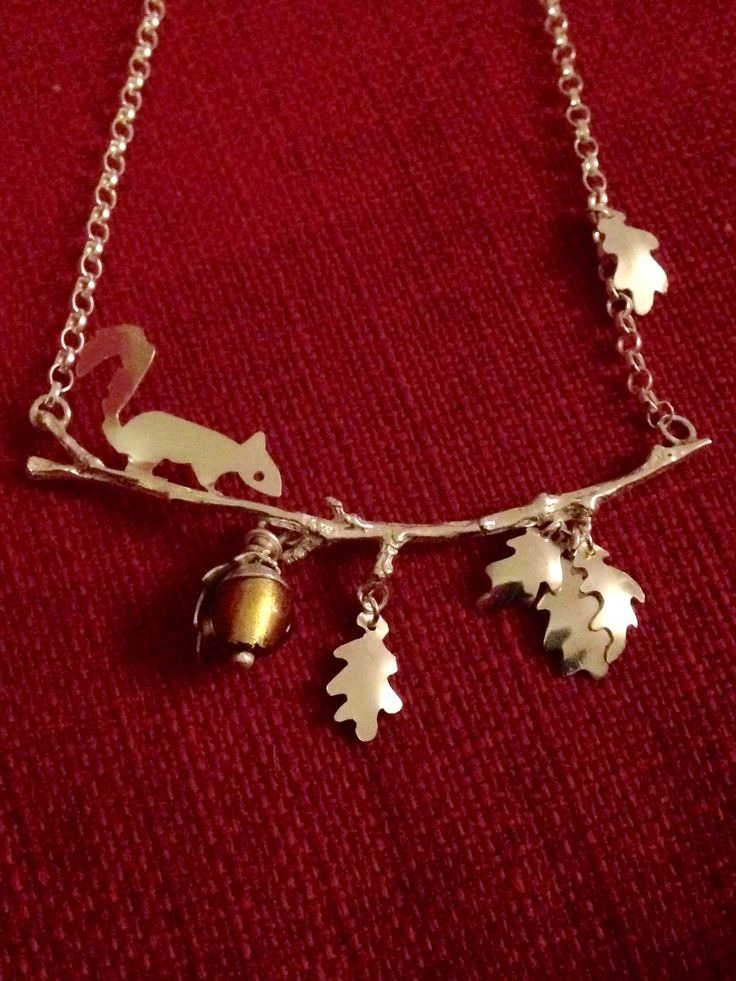 Squirrel necklace made from silver metal clay and silver sheet with glass foiled bead for acorn.