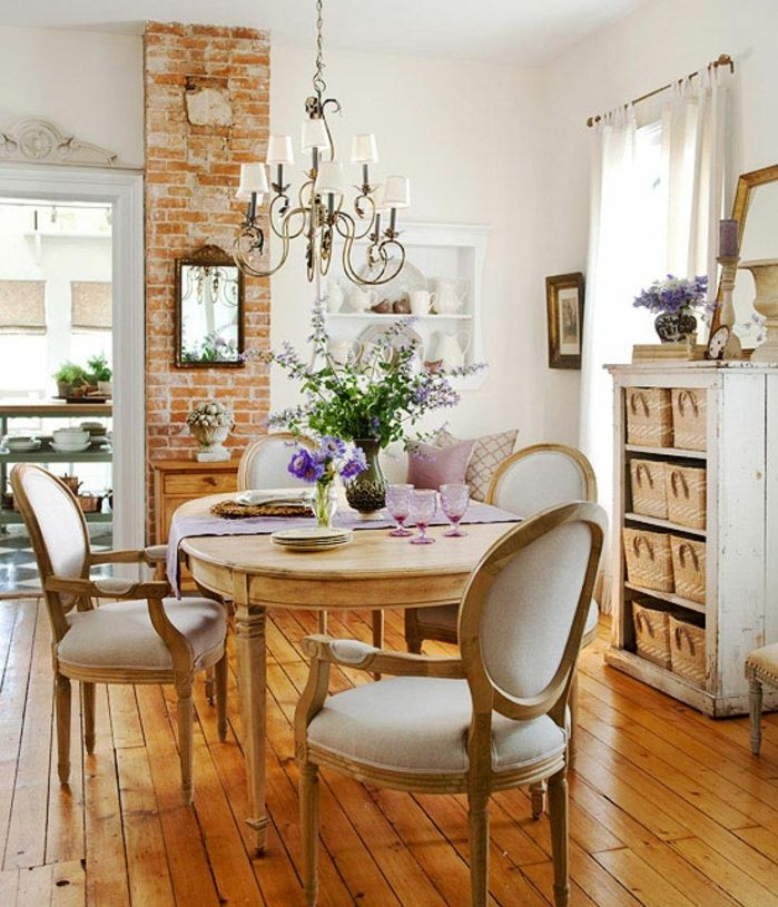 modele salle à manger campagne chic, chaises et table en bois, pan de mur en briques, meuble de rangement avec paniers en rotin, lustre baroque, deco shabby chic