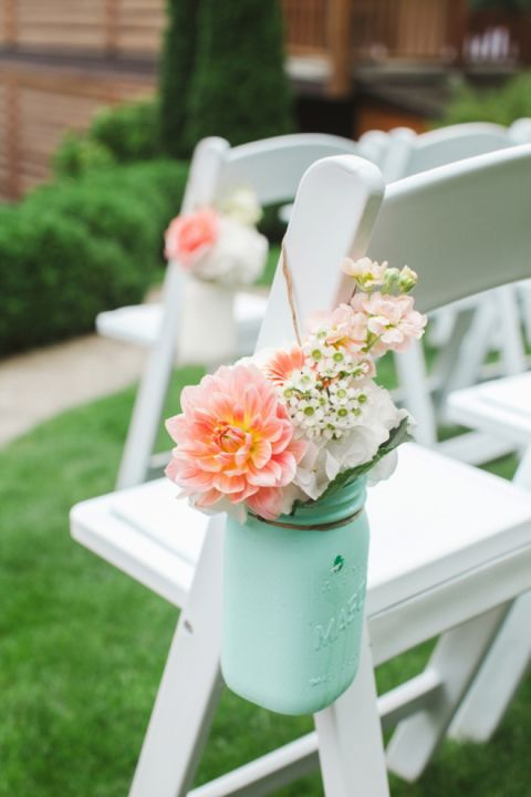 For an easy DIY way to decorate your aisle, paint some Mason jars in your color palette, fill them with flowers, attach some twine and hang them from the chairs.