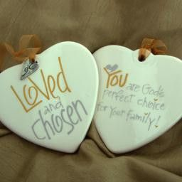 """Celebrate adoption with this calligraphy ornament. - White porcelain ornament - 3 1/2"""" - 3 3/4"""" diameter - Pewter charm - approximately 1/2"""" wide x 3/4"""" tall - Verbiage in silver / gold on front & bac"""