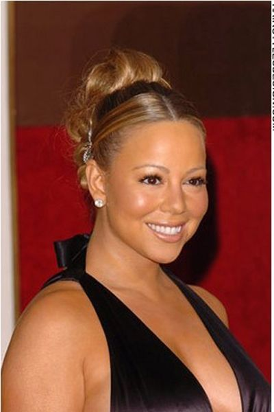 For this look, Mariah Carey has her long hair styled up into this classy and romantic, updo hairstyle. The hair is flattened to a smooth finish at the top just before it is curled and built up high towards the back. For a wedding, prom or any special occasion, this is a very glamorous style.The hair is long.The hair is coloured a dark brown with light brown highlights.