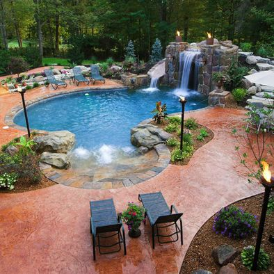 waterfall in my backyard for tranquility  pool has greenery around it  rock that feet can grip is used for flooring  tiki torches throughout the pool area for lighting