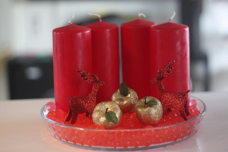 Denne adventskrans er lidt alternativ, fordi lysene står ved siden af hinanden, men det giver anledning til meget mere pynt foran og hvis man er glad for rød, så er den virkelig flot. Vandperlerne i fadet er store røde vandperler, og fordi de ligger i et klart fad, så er de ikke så dyb røde som man ofte forbinder julen med.