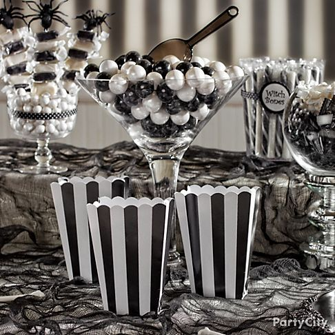 """Black and white striped popcorn boxes make your table feel like a haunted Victorian candy shoppe – and they're perfect for munching and mingling! Choose clear containers in elegant and gothic-looking shapes and fill them with candy sticks, gumballs, mints and candy skewers. Add ribbons and fun labels like """"witch bones,"""" and use silvery candle holders to add height. (Find glass containers and a to-die-for candy selection at your local Party City store.)"""
