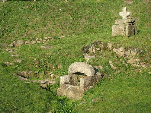 Fontaine de Kerderff, Larmor-Plage. Morbihan. Constituée d'une pierre en forme de U renversé, sa source alimente un petit bassin. Elle est surplombée par une croix encastrée dans une pierre trouée.