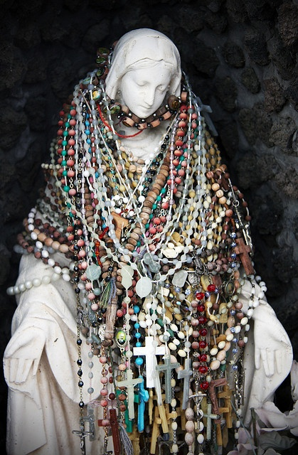 a Madonna covered in rosaries by passersby at a gas station