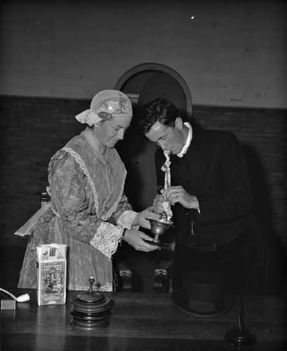 1965. In het friese plaatsje joure werd woensdagmiddag een huwelijk voltrokken in oud-fries costuum en volgens de eeuwenoude friese gebruiken. Zo steekt op deze foto de bruid de brand in de bruidegomspijp ten teken van haan trouw aan haar echtgenoot.