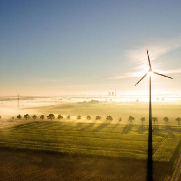 In una foto fatta con un drone, banchi di nebbia incontrano i raggi del sole mattutino su dei campi agricoli, sullo sfondo di una pala eolica a Sehnde, nella regione di Hannover, in Germania