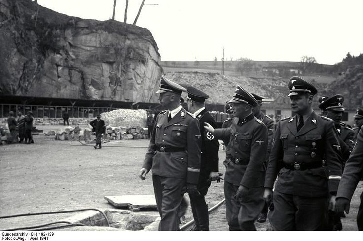 Heinrich Himmler visits KZ Mauthausen in April 1941. To his left is the camp commandant SS-Sturmbannführer Franz Ziereis. Nxt to the latter walks Himmler's chief-of-staff Karl Wolff. The actual location is Mauthausen's infamous quarry where thousands of prisoners met their deaths. Ziereis was tried and sentenced to death; he was executed on May24, 1945.