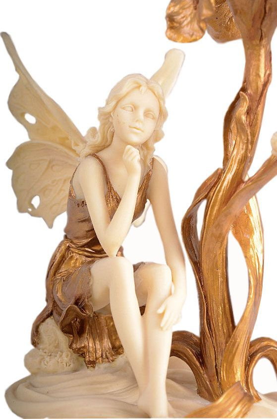 Świecznik+na+jedną+świecę+w+stylu+secesyjnym.+Mocowanie+dla+wysokiej+świecy+zostało+ukryte  w+rozkwitającym+pąku+kosaćca.+Pod+złotym+kwiatem+siedzi+zamyślona+kobieta-elf+z+motylimi+skrzydłami.+Skromna+sukienka+przewiązana+w+pasie,+odsłania+zgrabne+nogi+i+szczupłe+ręce.+Pogrążona+w+swoich+myślach+zdaje+się+nie+zwracać+na+nic+uwagi.+Świecznik+wykonany+z+konglomeratu+ceramiczno-alabastrowego+o+optyce+kości+słoniowej+i+złota.    Precyzyjne+wykonanie+figuralnej+sceny+czyni…