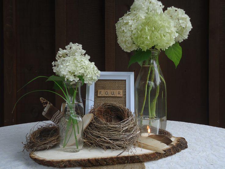 Reminds me of spring. Wooden slab base. Birds nest. Feathers. Votive candles. Vintage glass bottles. Hydrangeas (cream and pale green).   https://www.facebook.com/focalpointdesignsanddecor?ref=hl