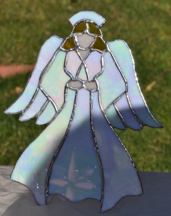 The angel is made of white iridescent glass,yellow artique transparent glass for her hair,and flesh opal glass for her hands and face. She stands 8 1/2 inches in height and is 7 inches in width. $85