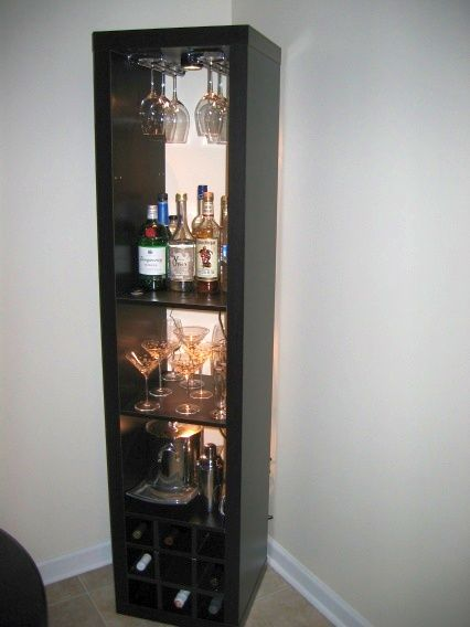 "Mike turns the Expedit bookshelf into a standing bar unit. He says, ""I needed a bar unit to hold some stemware, liquor, and wine. While my new place has tons of vertical space (3 meter high ceilings), I didn't have a lot of floor space in my dining nook. Therefore, I decided a tall, vertical [&hellip"