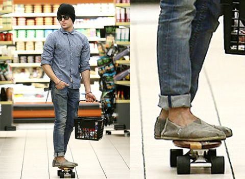 Zach Efron rocking Tom canvas shoes on a skateboard ride through the grocery store