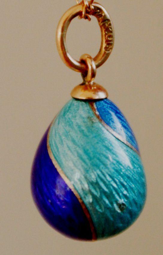 A Fabergé gold guilloché enamel pendant egg, workmaster Henrik Wigstrom, St. Petersburg, 1899-1908, in translucent light and dark blue enamels