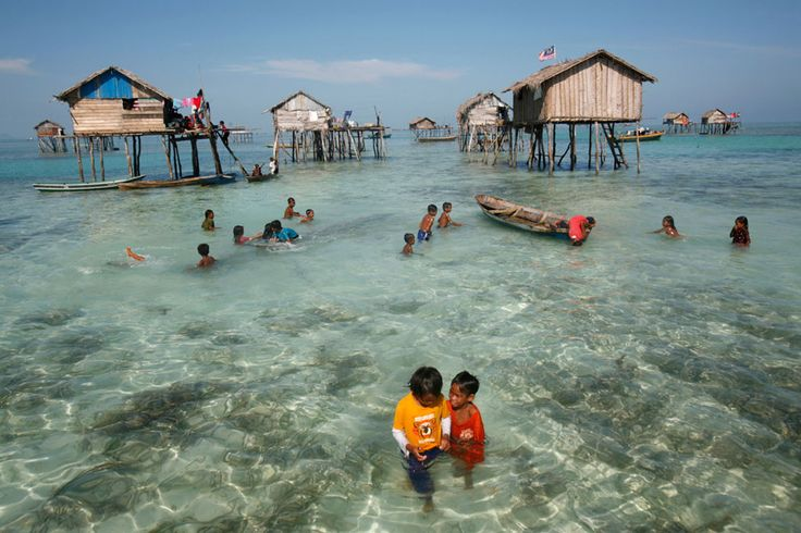 Young sea gypsies play in the water in the center of their neighborhood in the Sulawesi Sea in Malaysia's state of Sabah, on February 17, 2009. A community of 30 families of the indigenous ethnic group of sea gypsies maintain a nomadic and sea-based life without fresh water supply, TV nor electricity, and only go to land to bury the dead.