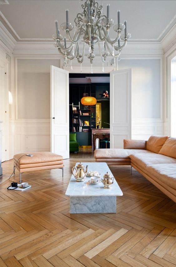 Salon avec grand lustre suspendu, table basse en marbre blanc, Parquet clair à bâtons rompus