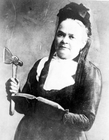 A portrait of Carrie Nation, notorious Temperance advocate, holding her bible and her hatchet. Ms. Nation was known in the years prior to Prohibition for her outspoken criticism of alcohol and a propensity for vandalism towards establishments that served spirits.