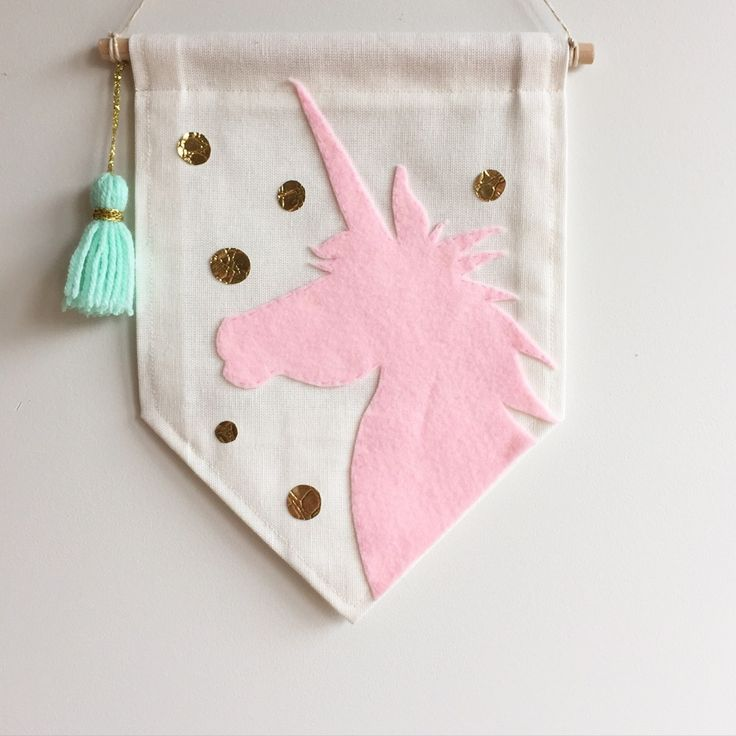 Beautifully detailed, hand cut and hand stitched felt pastel pink unicorn silhouette, with coordinating mint tassel trim.Single sided banner made from quality cotton fabric, machine stitched on all sides.W 20cm x L 27cmWooden dowel rod | L 23cm + coordinating string for hangingDesigns and colours may vary slightly to what is shown in pictureThis banner is pre-made and will be shipped within 5 days of purchasing.Please note, shipping costs are for standard pos...