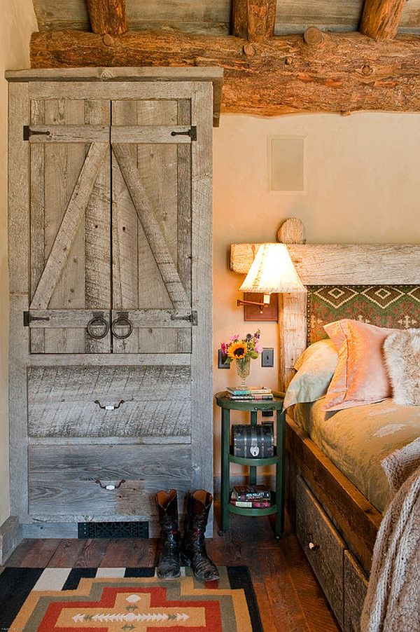 Cozy rustic bedroom design with built in wood shelving/dresser combined with the log beams crossing the wood ceiling creates a dramatic yet cozy bedroom setting.