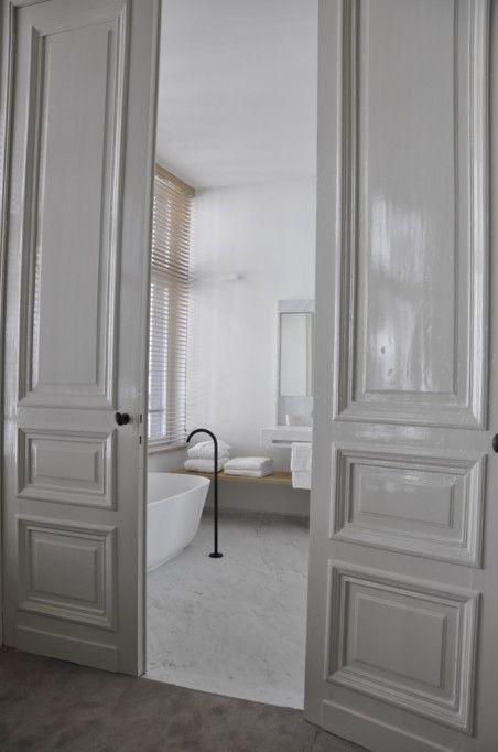 Wooden shelf/bench En suite bathroom inside a hotel by Belgian office AIDarchitecten. Classical modern.