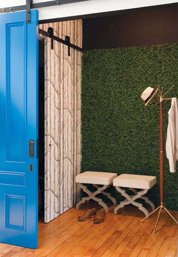 entry with blue sliding barn door, fake grass wall, and forest wallpaper