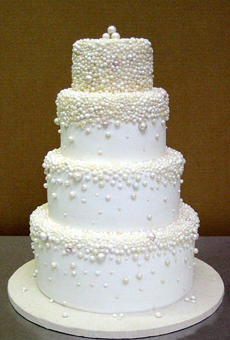 """Brides.com: . Each tier of this fondant-covered creation is covered with a cascade of opalescent sugar """"pearls.""""   Cake by Bijoux Doux"""