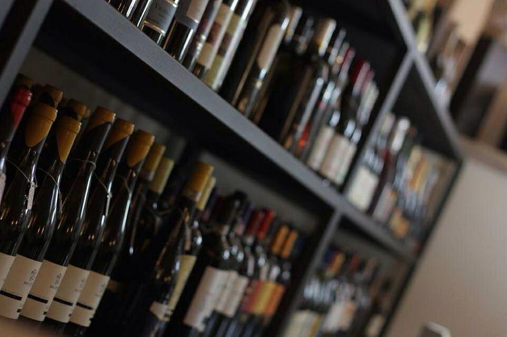 Uno scaffale con un'ampia scelta di bottiglie, anche da asporto.